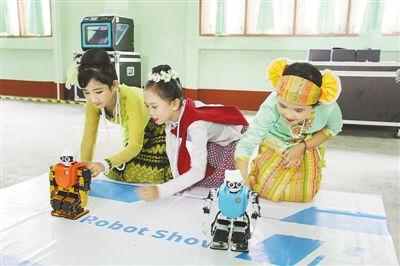 """日前,以""""体验科学·启迪创新""""为主题的中国流动科技馆缅甸国际巡展在缅甸内比都开幕。图为当地学生在体验智能机器人。 孙广勇摄"""