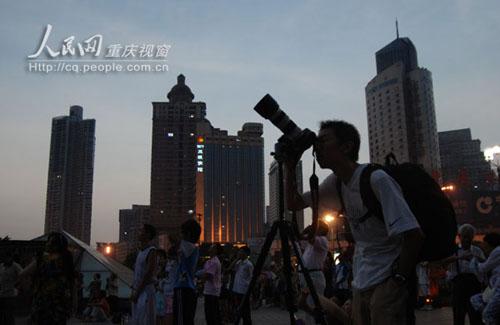 日全食期间,朝天门广场,一名摄影爱好者在拍摄这百年难遇的奇观记图片