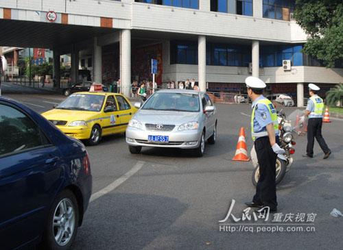 朝天门广场旁的转盘处,重庆市公安局渝中支队的交警正在维持交通秩图片